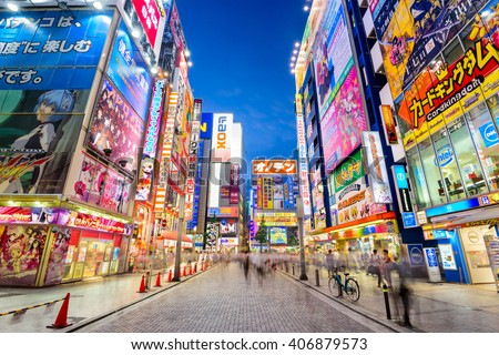 TOKYO, JAPAN - AUGUST 1, 2015: Crowds pass below colorful signs in Akihabara. The historic district electronics has evolved into the shopping area for video games, anime, manga, and computer goods. - stock photo