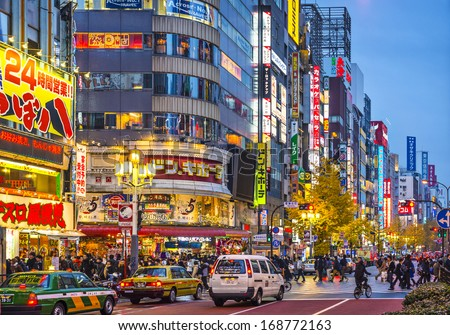 TOKYO, JAPAN - DECEMBER 15, 2012: Crowds walk under billboards in Shinjuku's Kabuki-cho district. The area is a nightlife district known as Sleepless Town. - stock photo