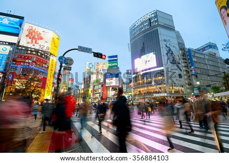 Tokyo, Japan - December 13, 2015: Pedestrians crossing at Shibuya Crossing. The Shibuya Crossing is one of the busiest in the world and it is a famous tourist spot. - stock photo