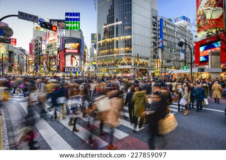 TOKYO, JAPAN - DECEMBER 14, 2012: Pedestrians walk at Shibuya Crossing during the holiday season. The scramble crosswalk is one of the largest in the world. - stock photo