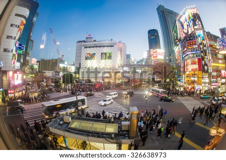 TOKYO, JAPAN - DECEMBER 19, 2014: Pedestrians walk at Shibuya Crossing during the holiday season, one of the busiest crosswalks in the world. - stock photo