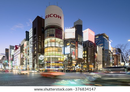 Tokyo, Japan - January 18, 2015:  Ginza shopping district at rush hour in Tokyo. The iconic  Sanaa Building  is at the background.  - stock photo