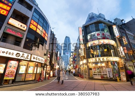 Tokyo; Japan -January 10; 2016: Street view of Nishi Shinjuku Shopping street whith several Japanese Restaurants on the sides. Mode Gakuen Cocoon Tower is at the background.  - stock photo