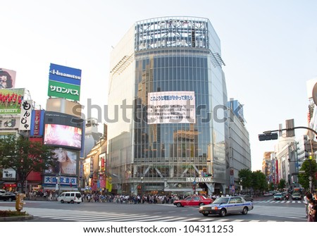 TOKYO, JAPAN - JULY 21: Unidentified people waiting to cross the Shibuya crossing that is one of the famous examples of a scramble crosswalk in the world on July 21, 2011 in Tokyo, Japan. - stock photo