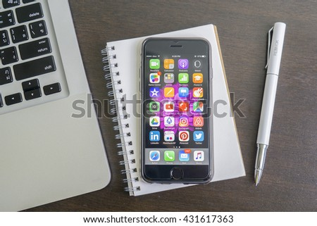 Tokyo, Japan - June 5, 2016:A new gray space black iPhone 6s with colorful screen on the wooden table. iPhone 6s was created and developed by the Apple inc.The iPhone is the top-selling phone . - stock photo