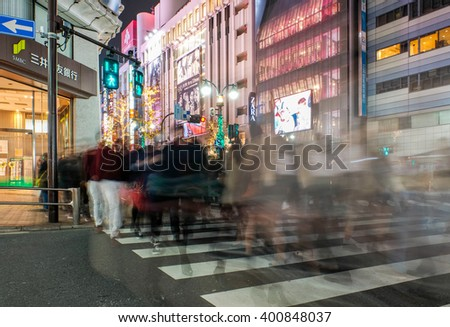 TOKYO, JAPAN - MAR 5, 2016: Pedestrians walk at Shibuya Crossing during the holiday season. The scramble crosswalk is one of the largest in the world. - stock photo