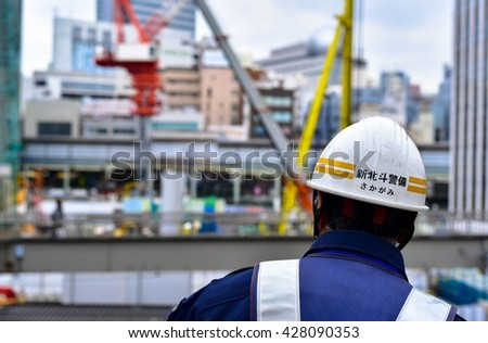 TOKYO, JAPAN - MARCH 2016: Japanese construction worker with blurred construction site in the background.  - stock photo