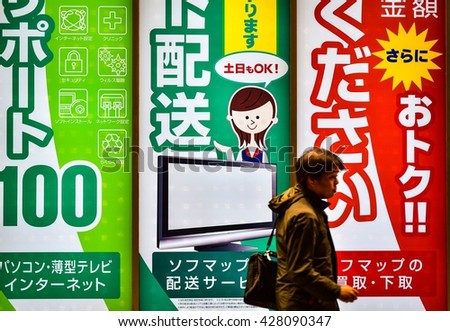 TOKYO, JAPAN - MARCH 2016: Japanese Shopper in front of neon signs in Akihabara district of Tokyo. - stock photo