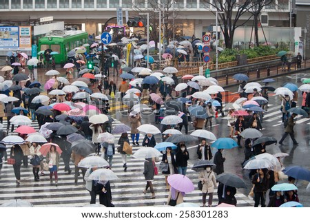 TOKYO, JAPAN - MARCH 20: People acrossing the crosswalk in raining day on March 20, 2014.Shibuya crossing is one of busiest places in Tokyo and is recognized thanks to being featured in multiple films - stock photo
