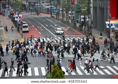 TOKYO, JAPAN - MAY 9, 2012: People walk the Hachiko crossing in Shibuya, Tokyo. Shibuya crossing is one of busiest places in Tokyo and is recognized thanks to being featured in multiple films. - stock photo