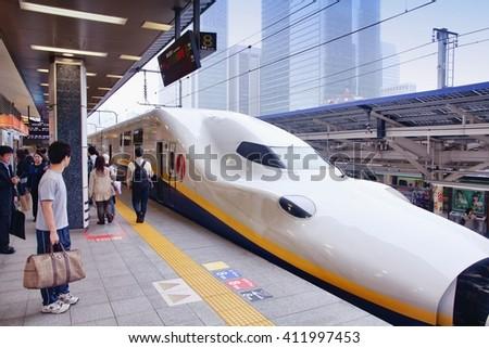 TOKYO, JAPAN - MAY 4, 2012: Travelers board Tohoku Shinkansen E4 series train at Tokyo Station. Hayate has top operating speed of 275km/h and is among fastest trains worldwide. - stock photo