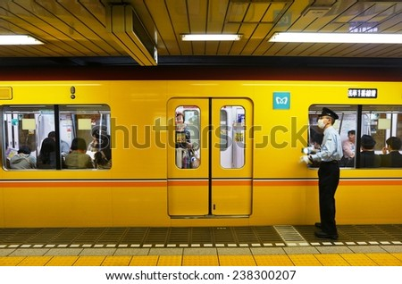TOKYO, JAPAN --NOVEMBER 2014-- A guard wearing a health mask pushes riders into a yellow Tokyo subway, which can get very crowded with Japanese commuters during rush hours. - stock photo