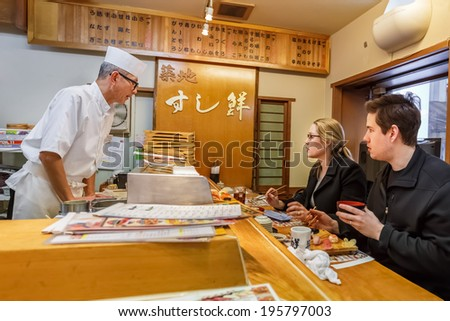 TOKYO, JAPAN - NOVEMBER 25: Japanese Sushi Chef  in Tokyo, Japan on November 25, 2013. Unidentified Japanese Sushi Chef prepares a dish of sushi for his customer - stock photo
