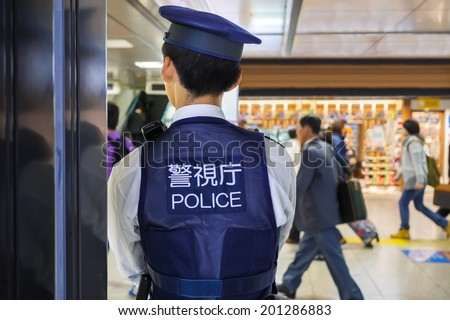 TOKYO, JAPAN - NOVEMBER 26: Policeman in Tokyo, Japan on November 26, 2013. Tokyo station provides maximun security by placing policemen in many areas of the station - stock photo