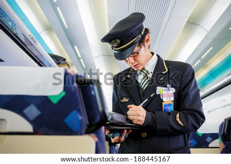 TOKYO, JAPAN - NOVEMBER 23: Train Steward in Tokyo, Japan on November 22, 2013. Train steward of JR train checks for ticket and makes fare adjustment for passenger - stock photo
