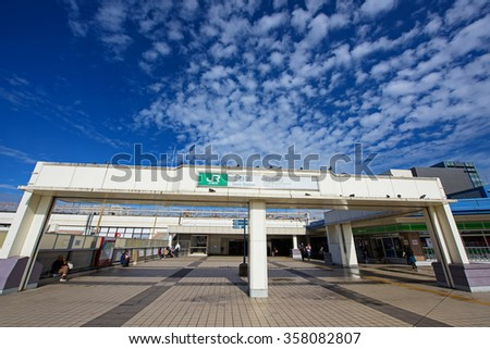 TOKYO, JAPAN - NOVEMBER 15, 2015: Unidentified poeple at Ueno station entrance on top levels against blue sky. Here is the station used to reach the Ueno district. - stock photo