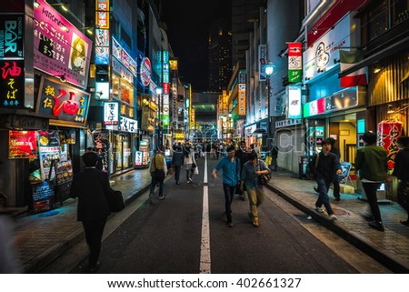 TOKYO - MAY 16, 2014: People walk in the night on the walking street of Shibuya district in Tokyo, Japan - stock photo