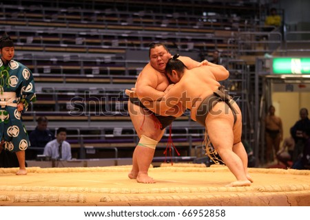 TOKYO - NOVEMBER 18: Two young sumo wrestlers in a tight grip in the Fukuoka Tournament on November 18, 2010 in Fukuoka, Japan. - stock photo