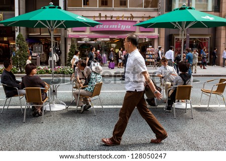 TOKYO-SEPT 20: The upscale Ginza district in Tokyo, Japan on Sept. 20, 2009. The famous Chuo Dori closes to cars on Sundays, sets up tables and becomes a pedestrian street to encourage shopping. - stock photo