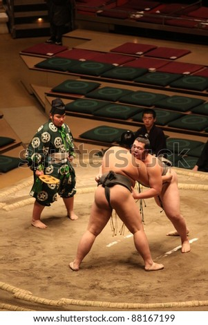 TOKYO - SEPTEMBER 17:  Two unidentified sumo wrestlers in a tight grip during the Tokyo Grand Sumo Tournament, September 17, 2011 in Tokyo, Japan. - stock photo