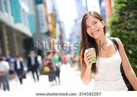 Tokyo urban woman commuter walking drinking coffee. Asian pedestrian going to work with crowd of people in the background commuting in the japanese city, Japan. - stock photo