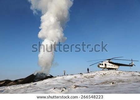 TOLBACHIK VOLCANO, KAMCHATKA, RUSSIA - FEBRUARY 2, 2013: Tourists and helicopter near the dangerous erupting Tolbachik Volcano on a sunny day. Russia, Far East, Kamchatka Peninsula. - stock photo