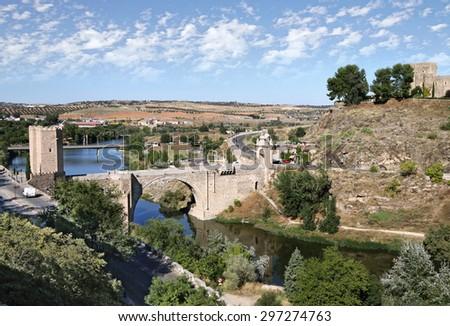 TOLEDO, SPAIN - OCTOBER 07, 2013:  Alcantara Bridge over the River Tagus in Toledo - stock photo
