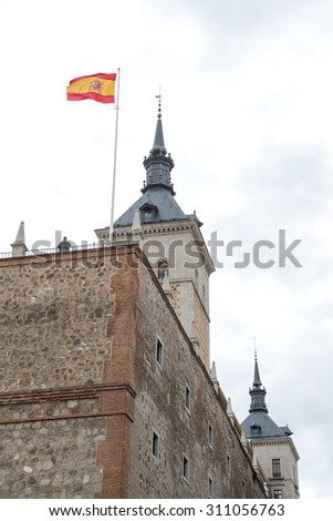 TOLEDO, SPAIN : Spanish flag and towers of Alcazar in the background - stock photo