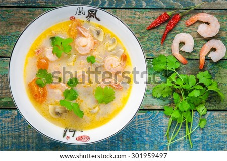Tom Yam soup in white bowl on wooden table top view - stock photo