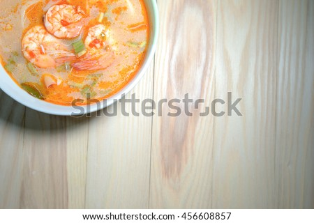 Tom Yum Goong spicy soup food cuisine in Thailand on wooden background. focus at shrimp - stock photo