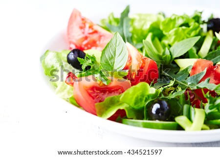 Tomato and cucumber salad with olives and pomegranate seeds - stock photo