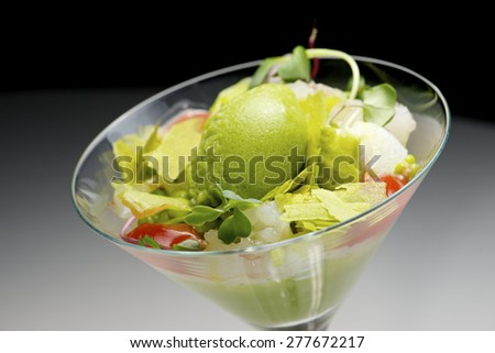 Tomato and green vegetables salad with cucumber cream served in crystal glass. - stock photo