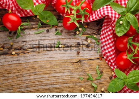 Tomato and herbs on wooden table - stock photo
