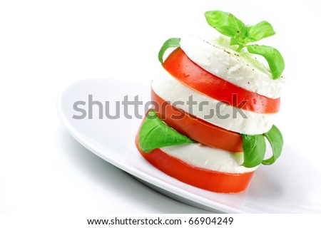 Tomato and mozzarella slices decorated with basil leaves on a plate and white background - stock photo