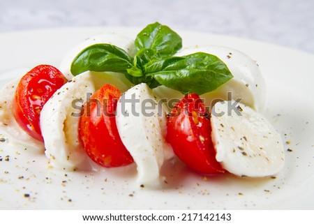 Tomato and mozzarella with basil leaves - stock photo