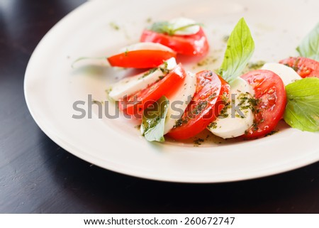 Tomato and mozzarella with basil leaves  - stock photo