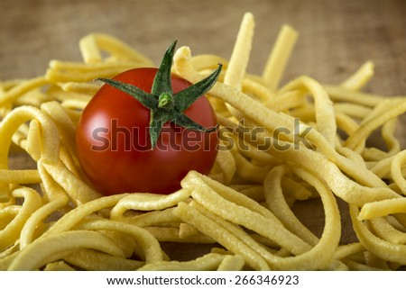 Tomato and noodles over old wood background - stock photo