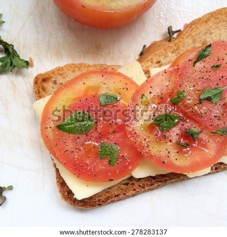 Tomato, cheese and basil on bread - stock photo