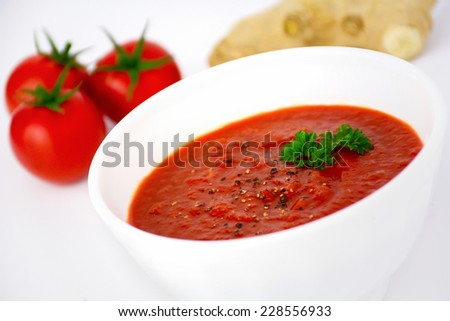 Tomato cream soup with ginger in white bowl decorated with parsley. Close up, angle view - stock photo