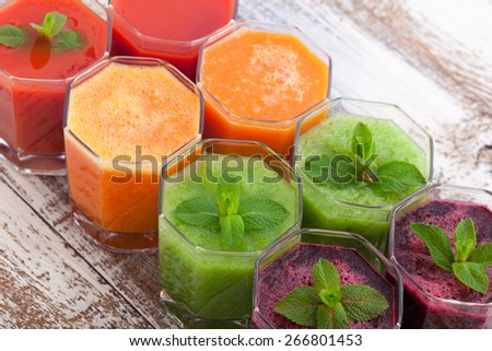 Tomato, cucumber, carrot, beet juices and vegetables on white wooden table top view. Closeup selective focus - stock photo