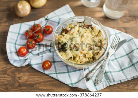 Tomato gratin with cheese and zucchini in baking dish - stock photo