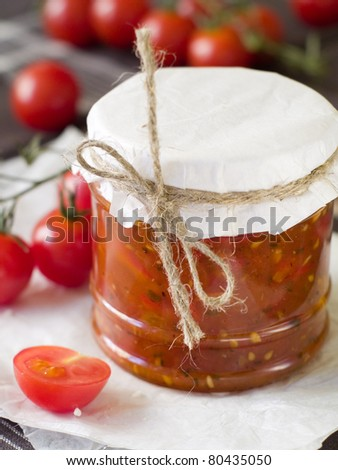 Tomato jam with pepper and garlic in glass jar. Selective focus, shallow doff - stock photo