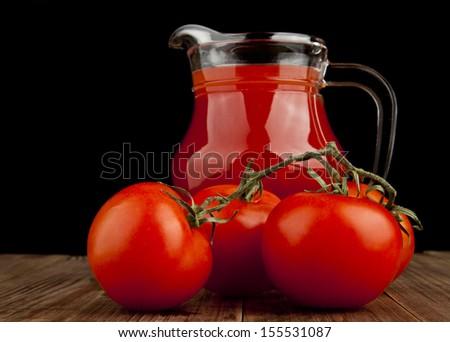 tomato juice and tomato on a black background - stock photo