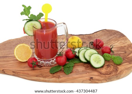 Tomato juice health drink with lemon, celery, cucumber, basil and mint herb on an olive wood board over white  background. High in vitamins, anthocyanins and antioxidants. - stock photo