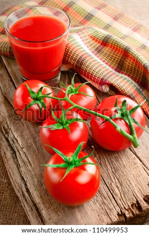 Tomato juice in glass and fresh tomatoes on vintage wooden cutting board and linen towel - stock photo
