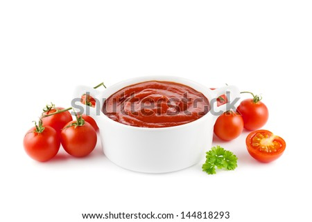 Tomato ketchup in a white bowl with tomatoes on white - stock photo