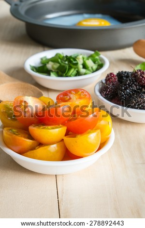tomato, mulberry side dish ingredient and fried egg in pan - stock photo