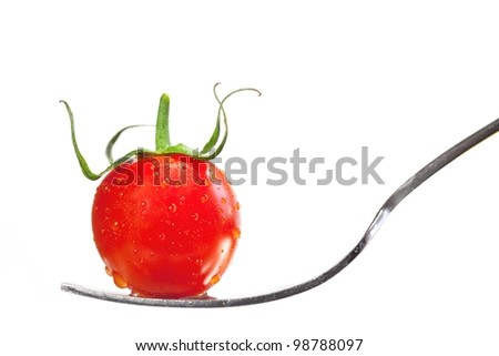 Tomato on a fork isolated on white - stock photo