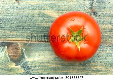 Tomato on wooden background - stock photo