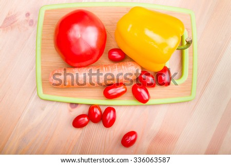 tomato paprika carrot on wooden board - stock photo